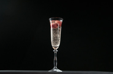 Glass of champagne with strawberries isolated on black background