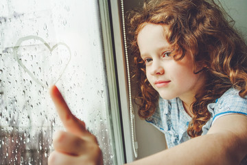 Happy child drawing heart on the window.