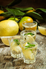 Carbonated lemonade with lemon slices and mint on an old wooden