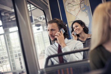 Two people seated on a bus talking on their cell phones