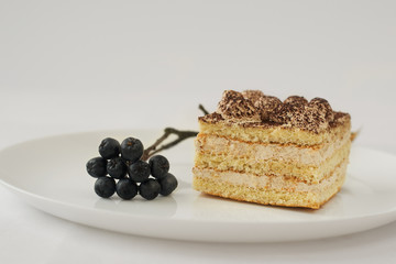 piece of white cake pie on plate sprig Aronia berries
