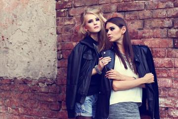 Two young fashion women posing outdoor. Wall mural