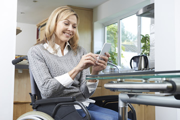 Disabled Woman In Wheelchair Texting On Mobile Phone At Home