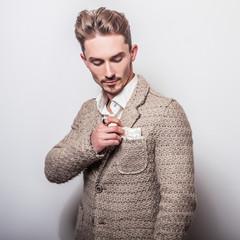 Elegant young handsome man in stylish beige costume. Studio fashion portrait.