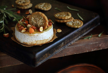 Baked cheese with almonds, rosemary, honey and crackers