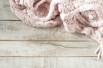 pink knitted scarf on wooden board with copy space for text.