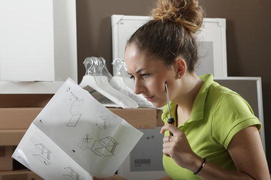 Femme lisant un mode d'emploi de meuble
