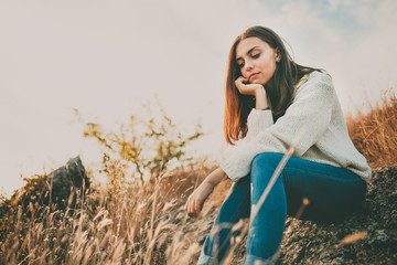 Teenage girl sitting alone on autumn cold day. Lonely sad young woman wearing warm sweater thinking and hesitating. Loneliness and solitude concept.