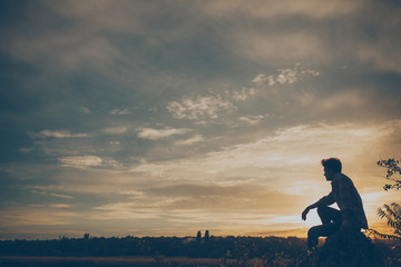Silhouette of young man sitting on sunset or sunrise. Confident teenage boy thinkig on cliff stone. Hope. Sadness. Freedom.