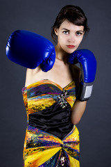 Woman in yellow dress wearing boxing gloves for competitive concept