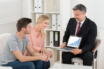 Financial Consultant Showing Graph To Couple