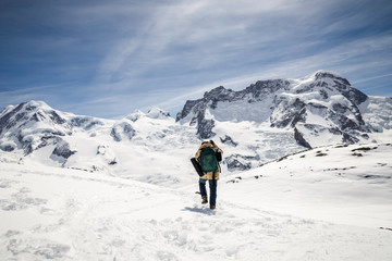 A man in camouflage winter coat and backpack standing in front of the background of snow mountain.