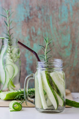 glass jars of cucumber and rosemary on wooden table