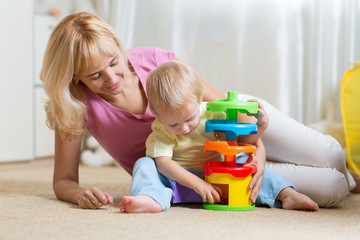 mother and kid playing with colorful logical toy