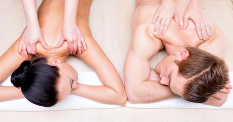 Beautiful couple lying  in a spa salon.