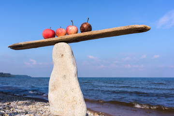 Apples in balance on narrow plank