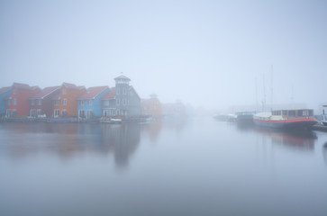 colorful building on water and boats in fog