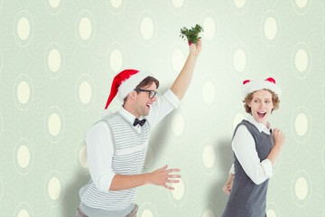 Composite image of playful couple with mistletoe