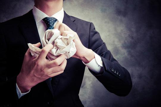 紙を丸めるビジネスマン