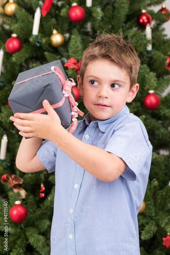 kleiner junge ist gespannt auf sein weihnachtsgeschenk. Black Bedroom Furniture Sets. Home Design Ideas