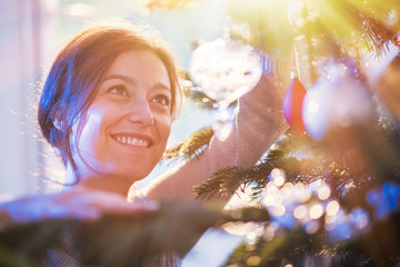 close up of a woman hanging a crystal ball in christmas tree