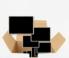 Opened carton box with old photograph templates, isolated on white.