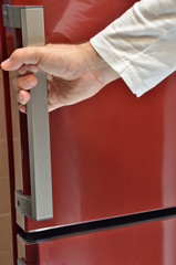 Hand on red refrigerator handle