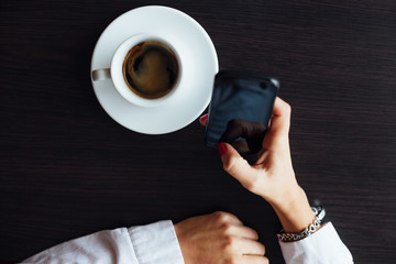 Top view of woman with cup of coffee using mobile phone