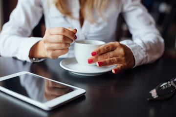 Woman with cup of coffee and tablet