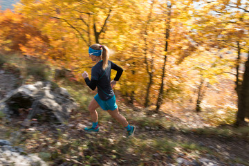 cross country trail female runner with long hair in autumn colorful forest