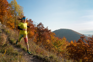 woman with long hair and glasses running on the trail in autumn mountains