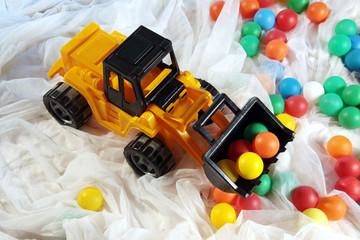 Spielzeug Bagger auf Stoff mit bunten Bällen