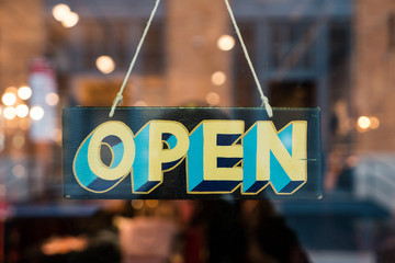 Open vintage wooden sign broad through the glass of store window Fototapete