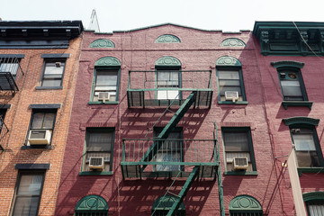 Facade of an old red brick apartment building in Little Italy, New York City.