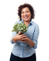 portrait of a mature woman holding a plant on a white background