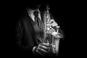 Detail of Saxophone and man hands isolated against black backgro