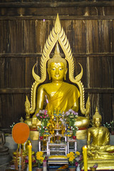 The Old Gold Buddha in ubosot at Thailand public temple - old wood wall
