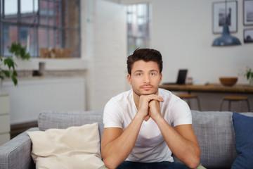 nachdenklicher mann sitzt auf seinem sofa