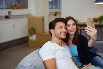 glückliches paar macht ein selfie nach dem umzug in die neue wohnung