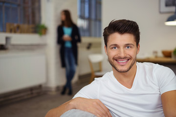 lächelnder mann sitzt in seinem wohnzimmer