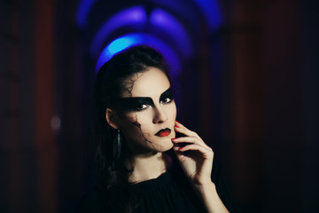 Beautiful woman with Halloween makeup. Close up street night portrait. Toned