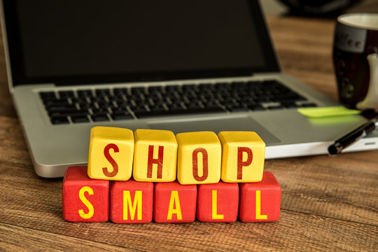 Shop Small written on a wooden cube in front of a laptop