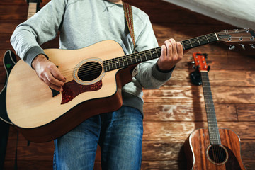 man playing guitar. Guitars on wall on background, love music concept