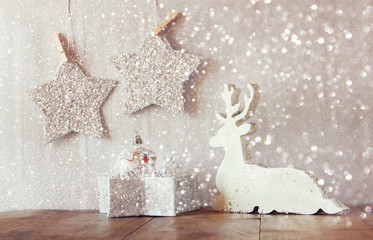 image of white wooden reindeer and glitter stars hanging on rope over glitter silver background. retro filtered