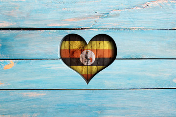 Love Uganda. Heart and flag on a blue wooden board Wall mural