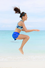 Crossfit fitness Asian woman on beach doing jump squat plyometric training exercises by jumping and touching knees as part of a full body core workout and active lifestyle.