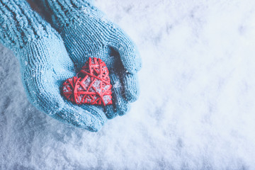 Woman hands in light teal knitted mittens are holding beautiful entwined vintage red heart on snow. Love, St. Valentine concept.