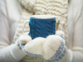 Woman hands in white and blue mittens holding a cozy knitted cup with hot cocoa, tea or coffee. Winter and Christmas time concept.