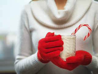 Woman hands in woolen red gloves holding a cozy mug with hot cocoa, tea or coffee and a candy cane. Winter and Christmas concept.