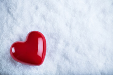 Red glossy heart on a frosty white snow background. Love and St. Valentine concept